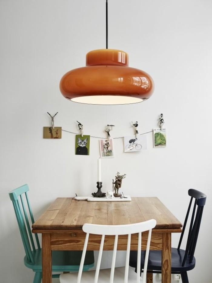 hölzerner-Tisch-bunte-Stühle-Leuchte-in-vintage-Stil