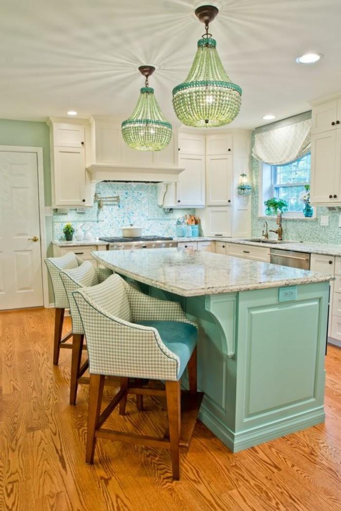 luxuriöse-Küche-in-türkis-Farbe-Kristall-Kronleuchter-stilvolle-bequeme-Sessel-Kücheninsel
