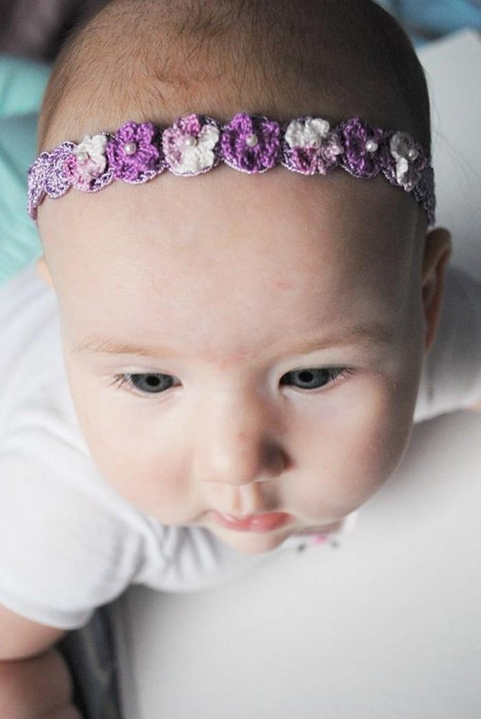 süßes-Baby-mit-lila-Haarschmuck-Blumen
