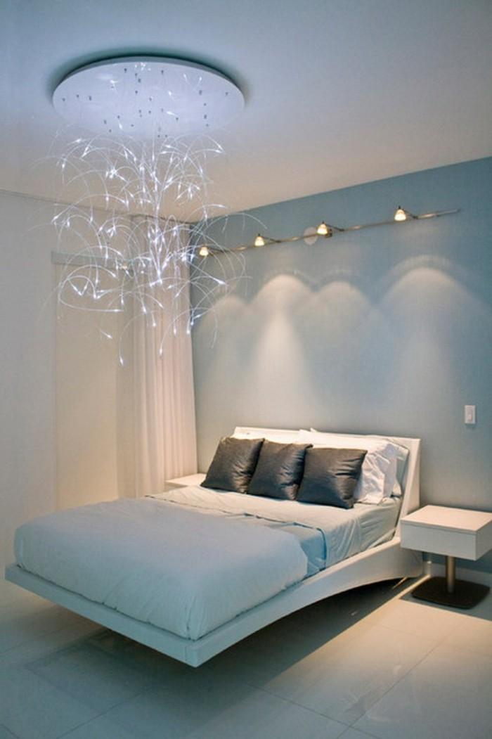 unikaler-kronleuchter-im-attraktiv-gestalteten-schlafzimmer-mit-weißem-bett