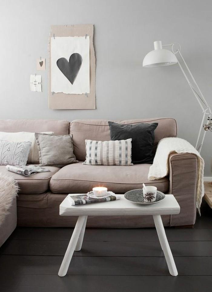 wohnzimmer-in-beige-schickes-sofa-viele-dekorative-kissen-lustiges-bild-mit-einem-herz-an-der-wand