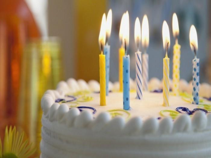 15-weiße-Geburtstagstorte-mit-leckerer-Glasur-und-bunten-Kerzen