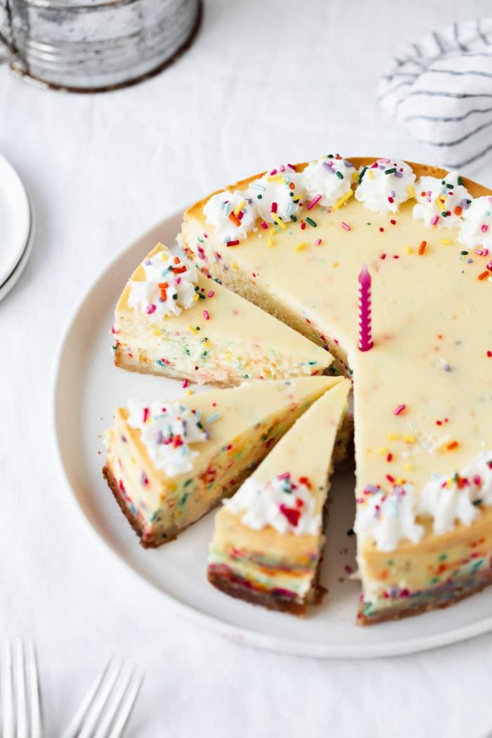 cheesecake geburtstagskuche für anfänger dekoriert mit bunten streuseln pinke kerze in der mitte leckere ideen zum geburtstag