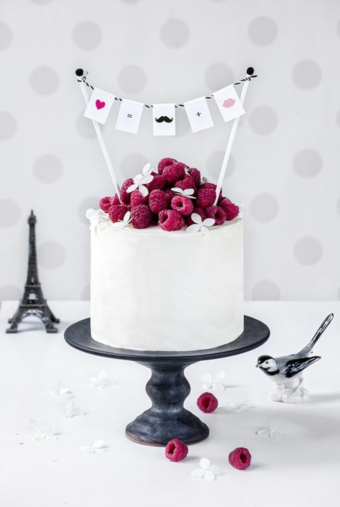 elegante-weiße-Geburtstagstorte-dekoriert-mit-Himbeeren