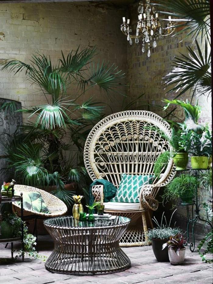 exotische-Atmosphäre-schaffen-Barock-Kronleuchter-Rattanstühle-mit-grünen-Sitzkissen-viele-Pflanzen