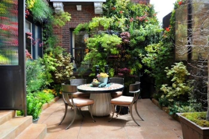 gartenideen-für-kleine-gärten-kleiner-runder-tisch-und-viele-grüne-pflanzen