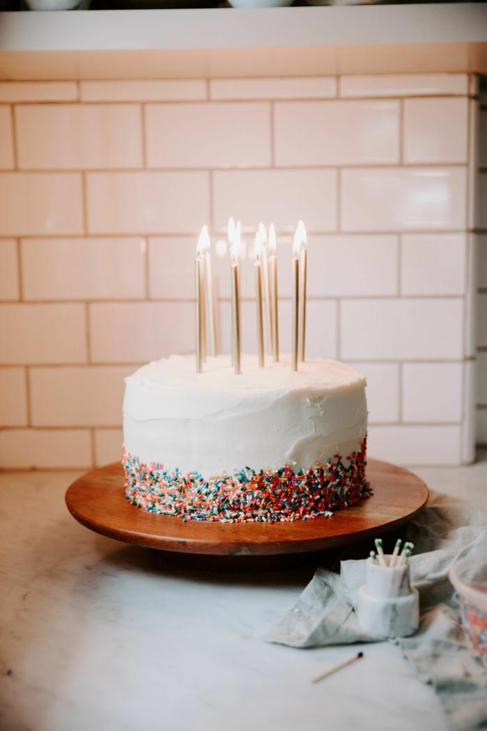 ideen geburtstagskuchen erwachsene vanill tetorte mit bunten sträuseln angezündete kerzen tortenständer holz farbe leckere torte inspiration