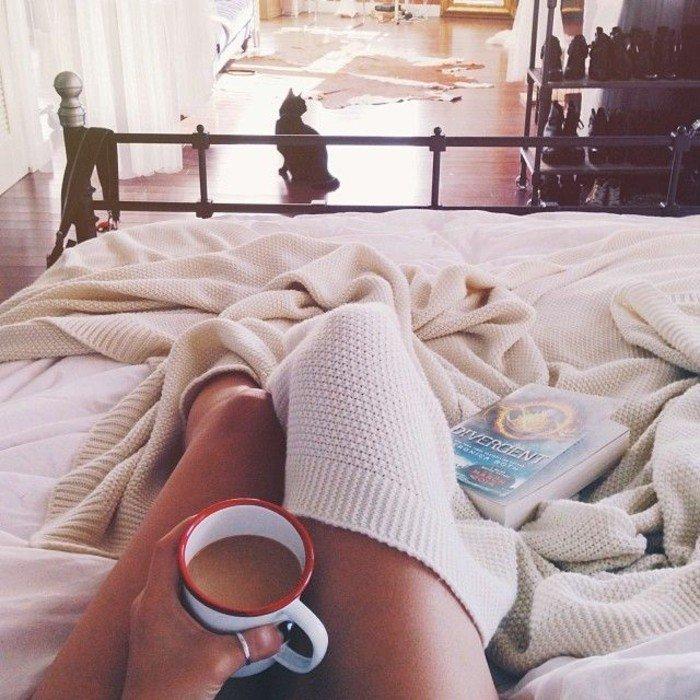 mit-einer-Tasse-heißes-Getränk-im-Bett-liegen