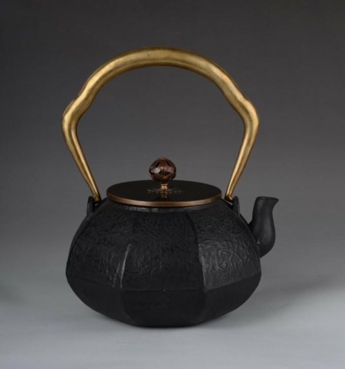 schwarze-japanische-teekanne-mit-goldenem-henkel