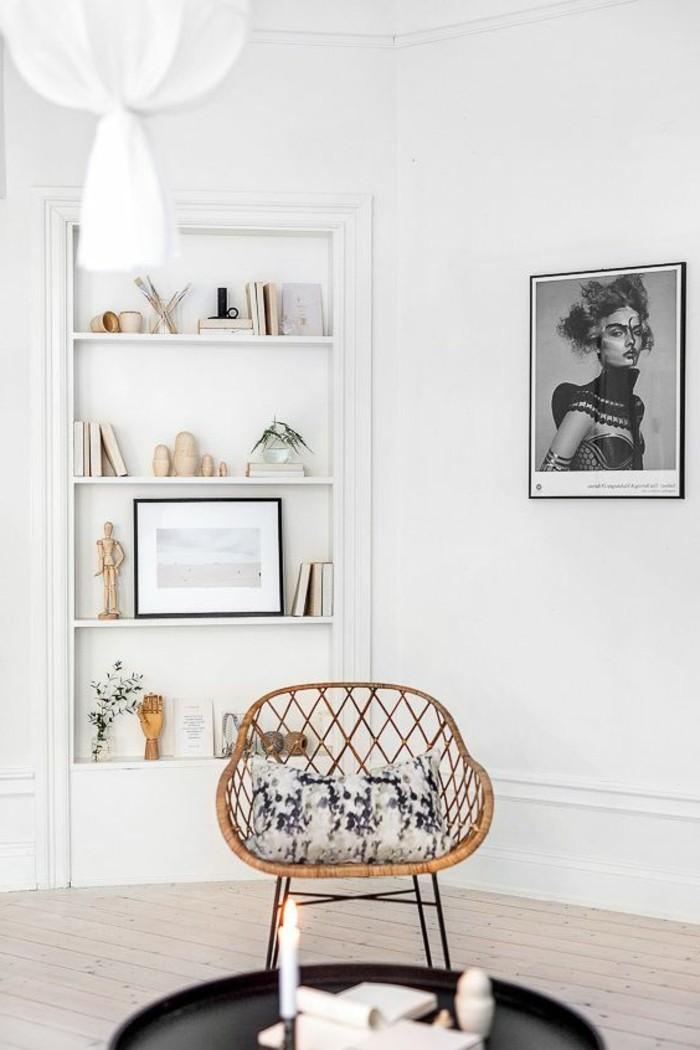 weißes-Interieur-mit-artistischen-Elementen-Bücherregale-Rattanstuhl