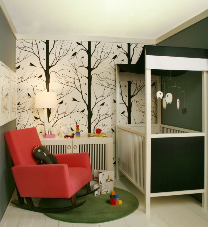 kreatives-modell-babyzimmer-mit-interessanten-wandtapeten-roter-sessel-neben-dem-babybett