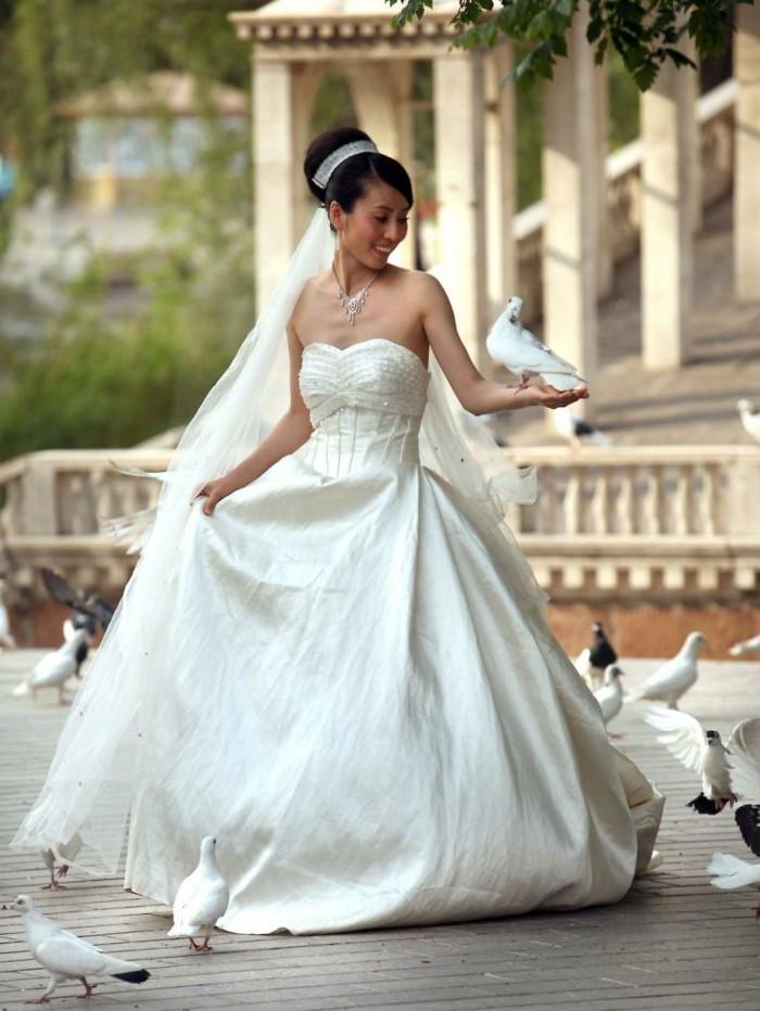Weisse-Hochzeitstauben-umgeben-die-Braut