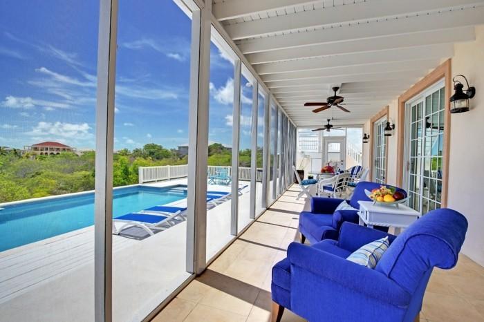 wunderschöne-gläserne-wände-und-blaue-sessel-modernes-haus-mit-panorama