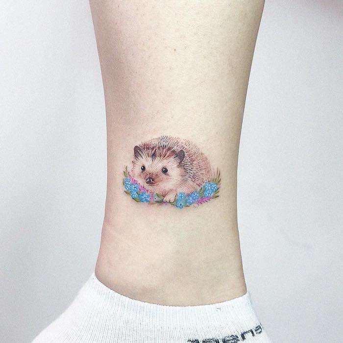 Farbiges Tattoo an der Wade, kleiner Igel und blaue Blumen, kleine Tattoos für Frauen