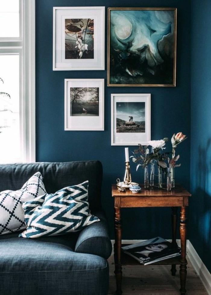 gemütliches-wohnzimmer-gestalten-accessoires-fotos-weiße-bilderrahmen-blaue-wand-antik-holztisch