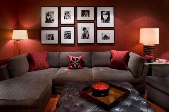 gemütliches-wohnzimmer-gestalten-accessoires-poster-rote-wand-kissen-dunkles-sofa-lampen