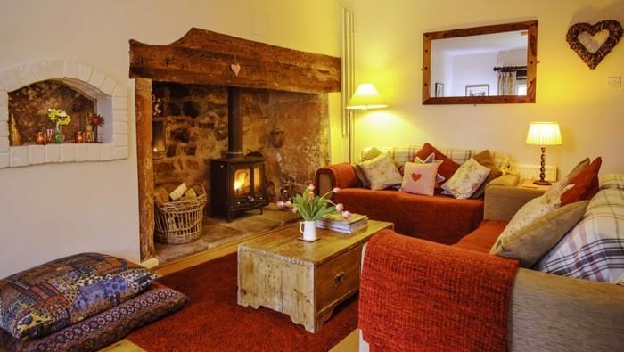 gemütliches-wohnzimmer-gestalten-kaminofen-sofa-orange-spiegel-holzrahmen-korb