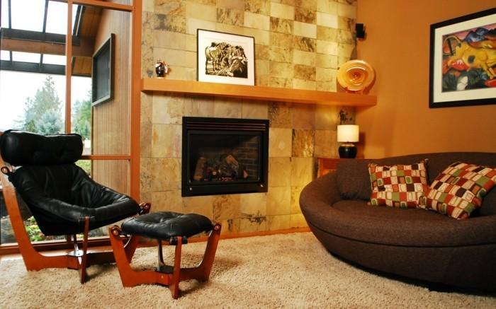 gemütliches-wohnzimmer-gestalten-leder-sessel-sofa-dunkle-farben-kaminoffen-steinverkleidung-karokissen
