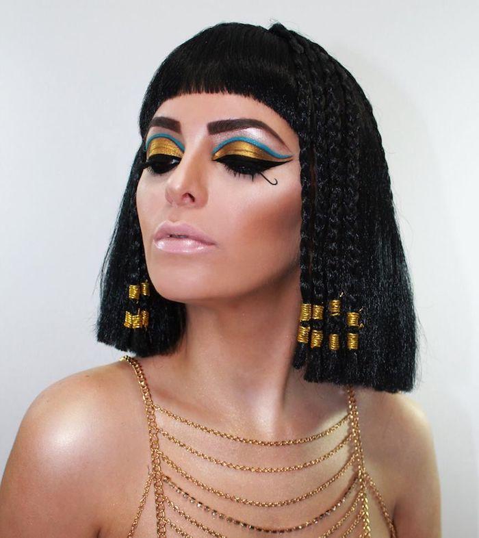 Cleopatra schminken, Goldener und blauer Lidschatten, rosa Lipgloss, Bob Haarschnitt mit Zöpfen und Pony