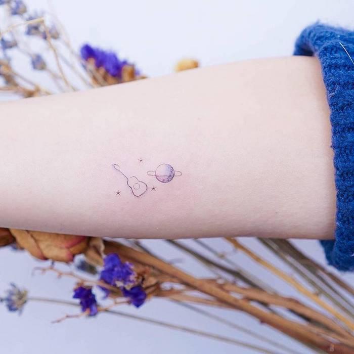 Mini Tattoo am Unterarm, kleine Gitarre und Saturn, kleines farbiges Tattoo für Frauen