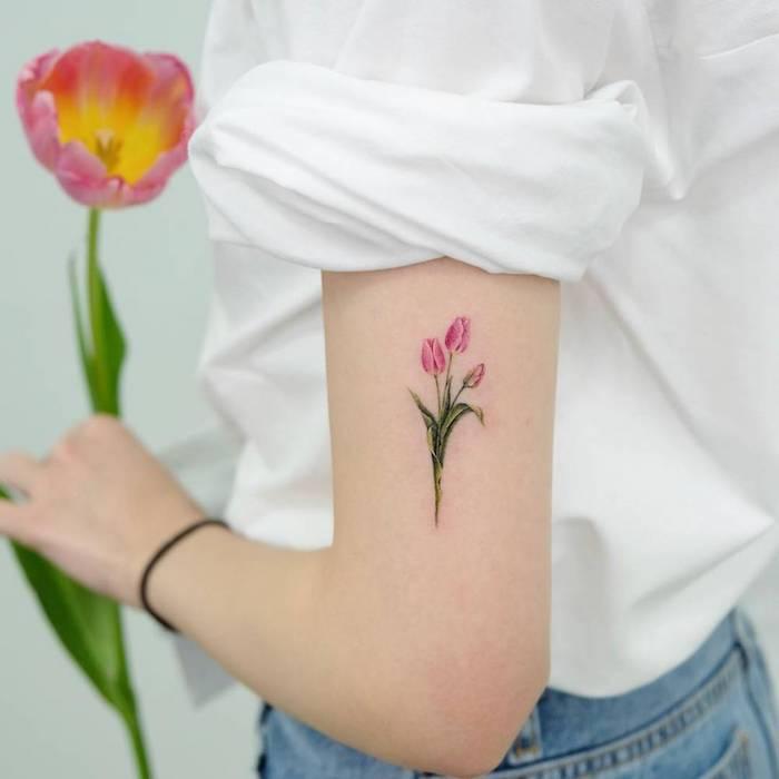 Kleines realistisches Tattoo am Oberarm, kleiner Tulpenstrauß, rosafarbene Tulpen, Blumen Tattoo