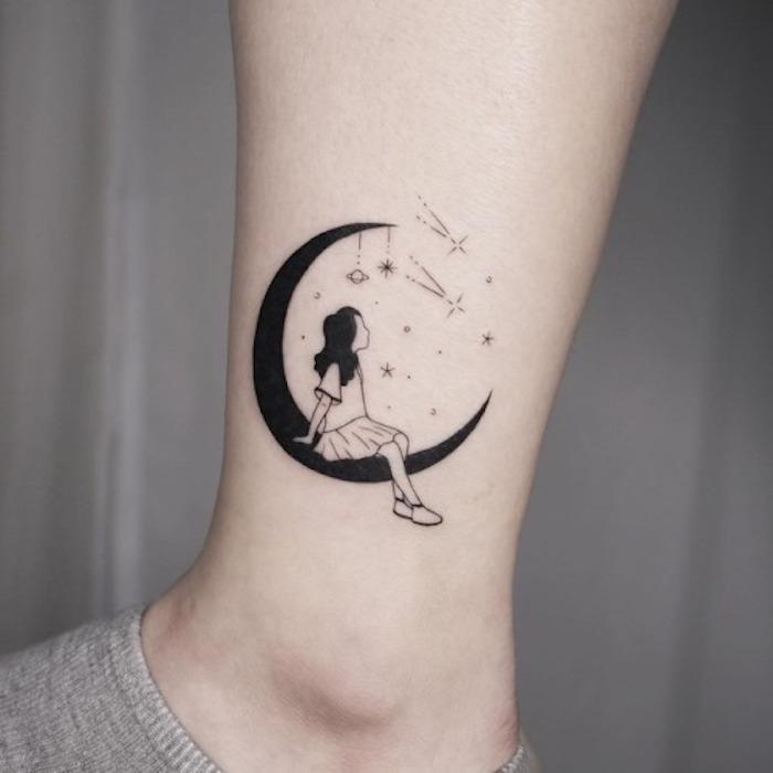 Schwarzes Tattoo am Knöchel, Mädchen sitzend auf dem Mond, kleine Planeten und Sterne, Mädchen mit Shirt und Rock