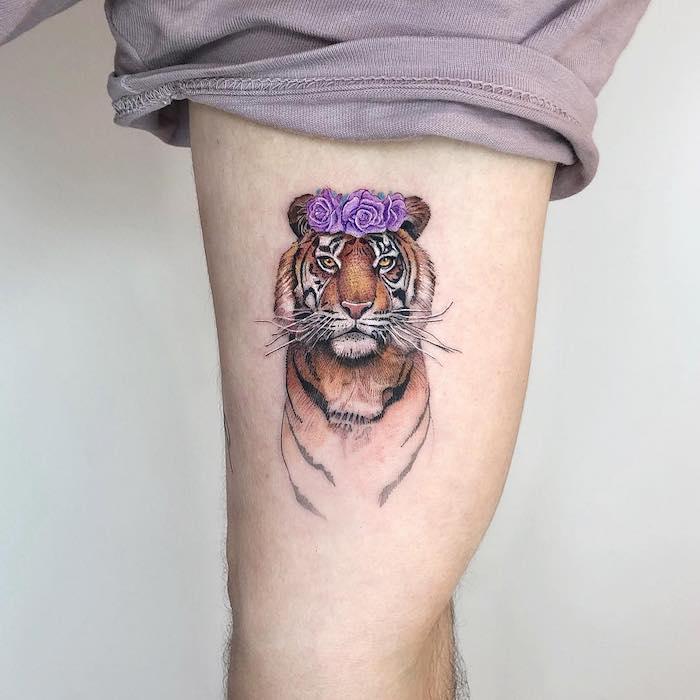 Tiger Tattoo am Bein, farbiges Tattoo am Oberschenkel, Tiger mit lila Rosen auf dem Kopf