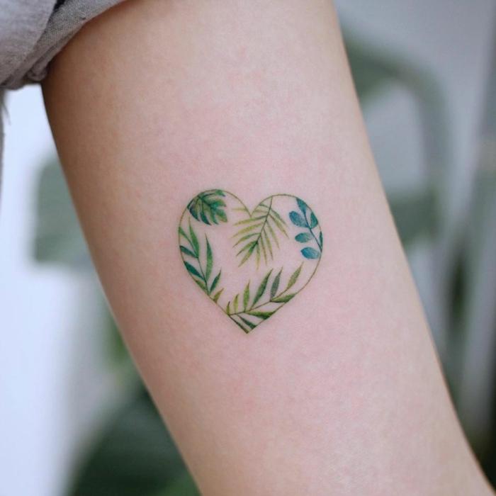 Kleines Herz Tattoo am Oberarm, grünes Herz mit Blättern darin, Frauen Tattoo Ideen