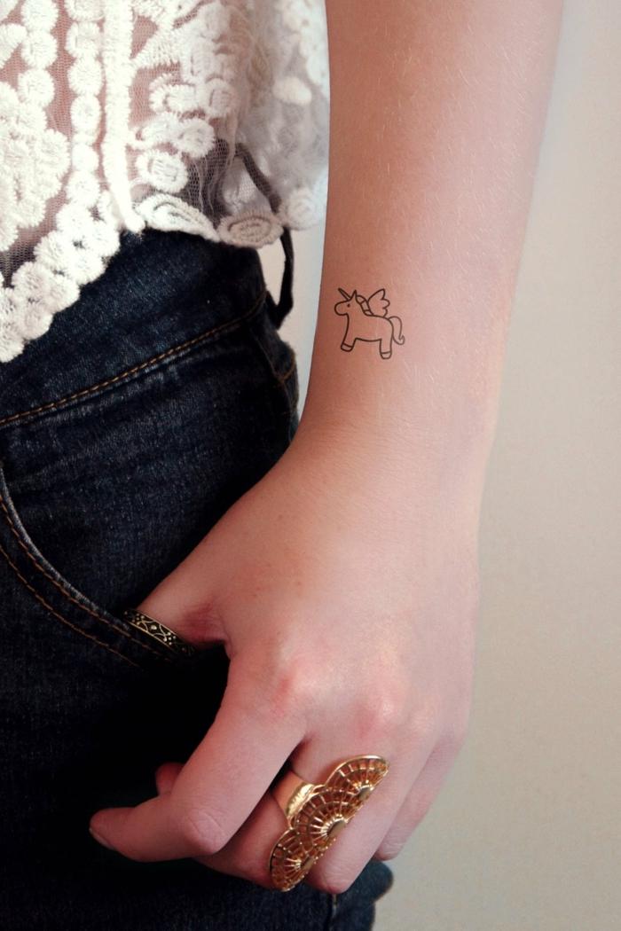 Kleines Tattoo am Unterarm, süßes Tattoo Motiv, Einhorn Tattoo, massiver goldener Ring, schwarze Jeans und weißes Top