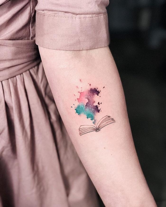 Schönes farbiges Tattoo am Unterarm, geöffnetes Buch und bunte Wolke, Symbol für Magie