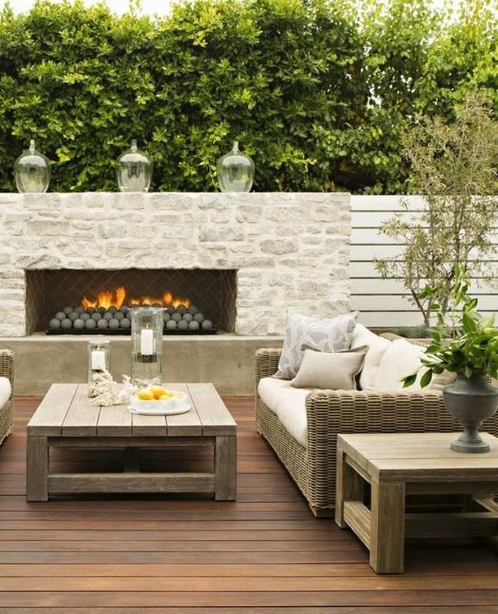 moderne-gartengestaltung-mit-sichtschutz-kamin-rattan-loungemöbeln-und-couchtisch-aus-holz