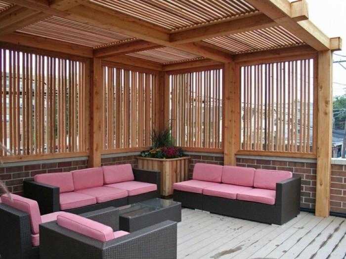 moderne-rosige-sofas-unter-einer-schicken-pergola-aus-holz