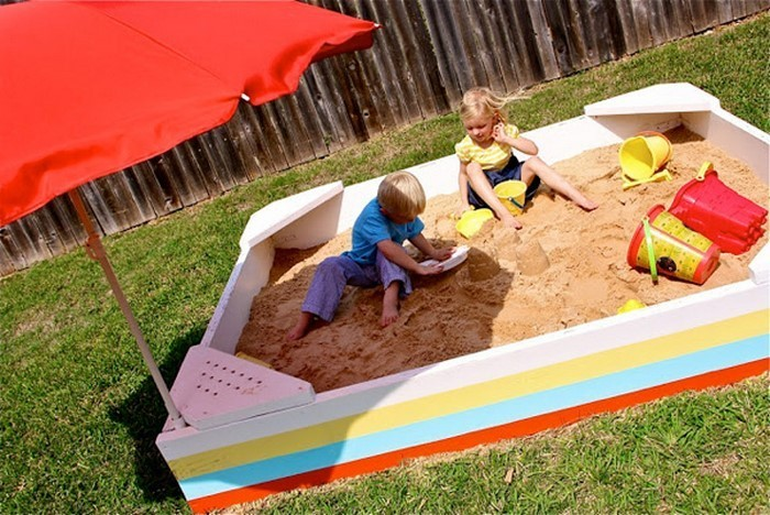 sandkasten-selber-bauen-glueckliche-Kinder-im-Sandkasten