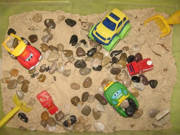 sandkasten-selber-bauen-kleine-Steine-und-Spielzeuge