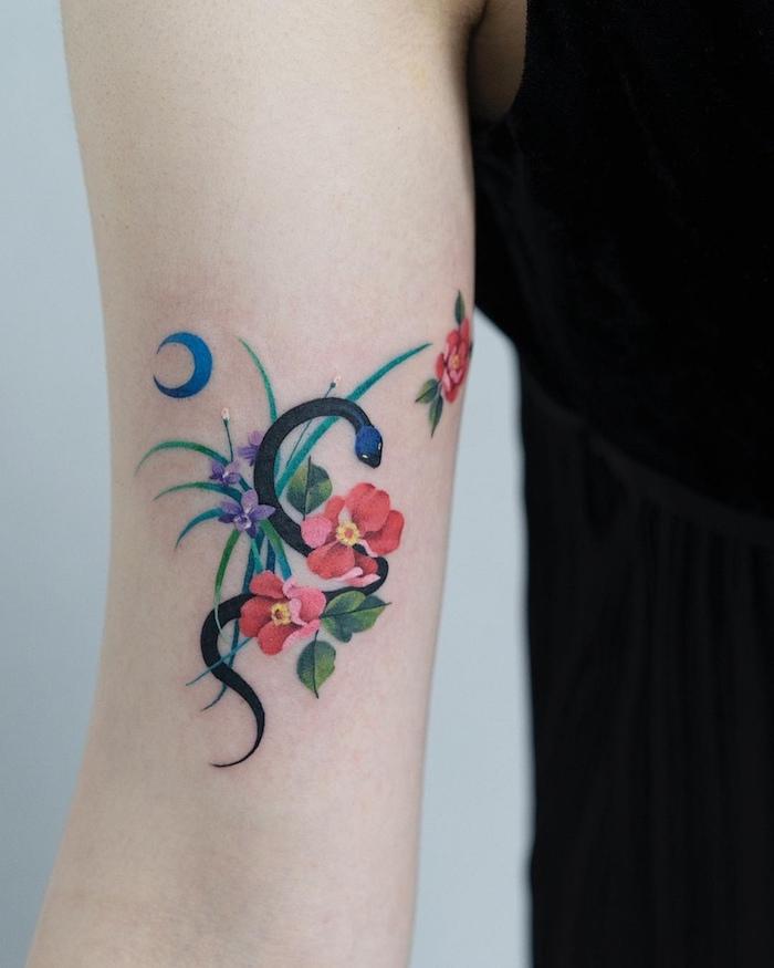 Kleines farbiges Tattoo am Oberarm, schwarze Schlange, bunte Blumen und blauer Halbmond