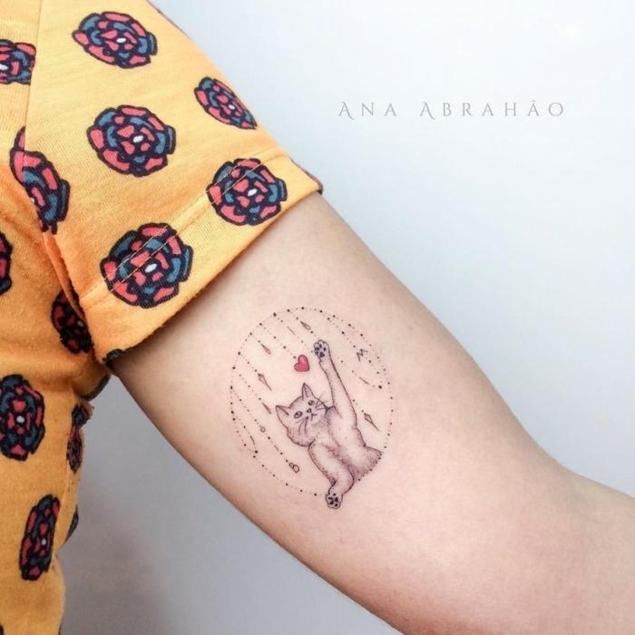 Kleines Tattoo am Oberarm, süßes Katzen Tattoo, Katze und kleines rotes Herz, gelbes Top mit Blumenmuster