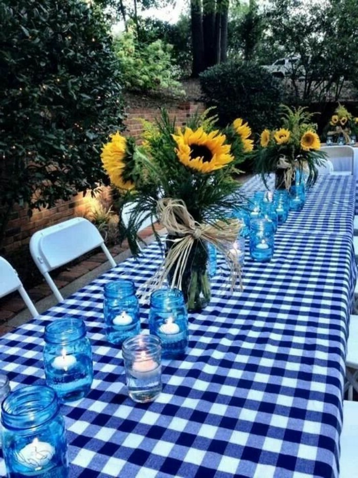 Einfache-Tischdeko-Sonnenblumen-und-Kerzen-in-blauen-Gläsern