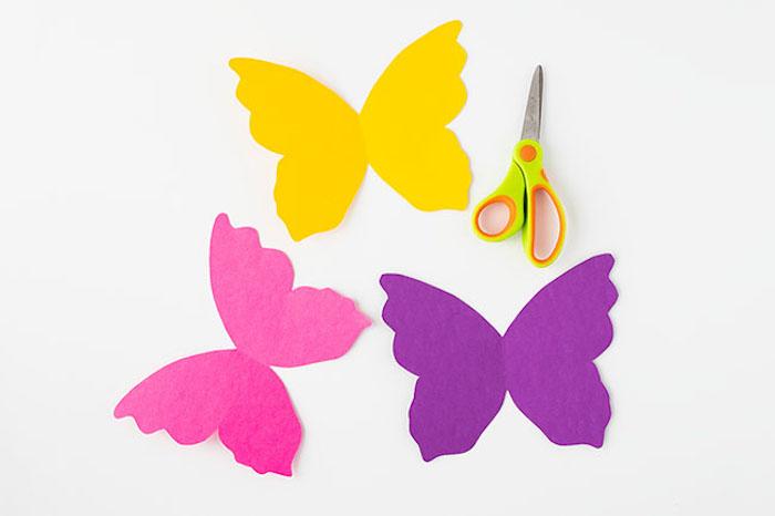 Schmetterlinge basteln mit Kindern, Flügel aus Karton schneiden, an Klorollen kleben
