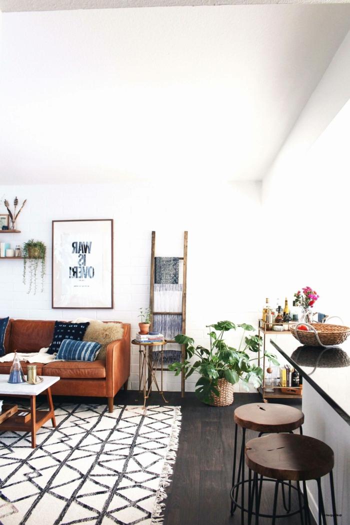 kleines Wohnzimmer einrichten, geometrischer Teppich, grüne Pflanze, Sofa aus Leder in braun