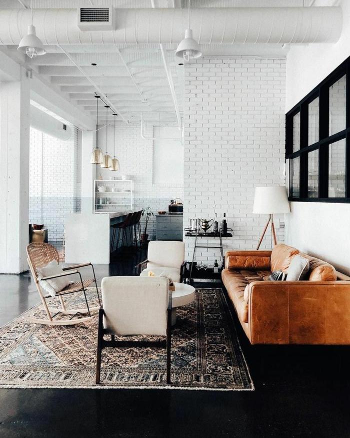 Backsteinwand in weiß, Sofa aus Leder in braun, weiße Stühle, Beleuchtung aus Metall, Wohnzimmereinrichtungen