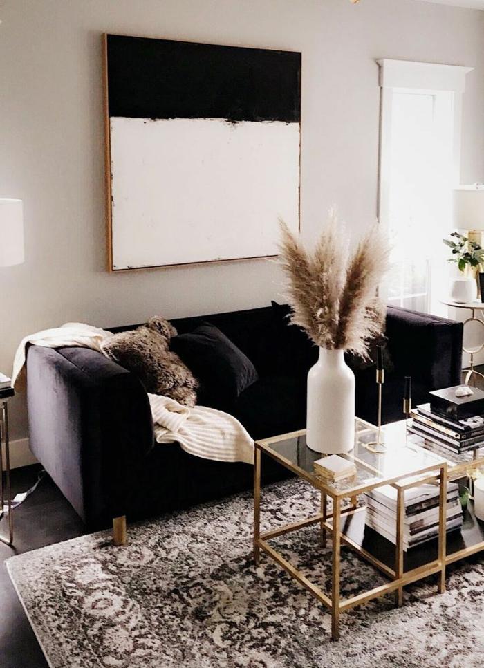kleines Wohnzimmer einrichten, Sofa in blau, Kaffeetische und Bücher, artistisches Gemälde an der Wand