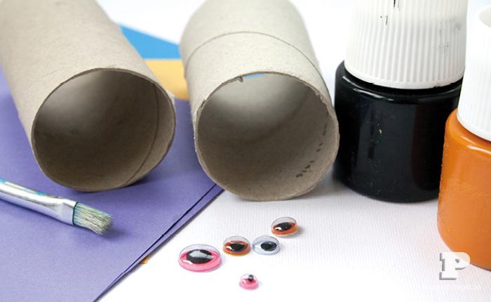 Materialien für DIY Halloween Monster, zwei Klorollen, schwarze und orange Acrylfarbe und Wackelaugen