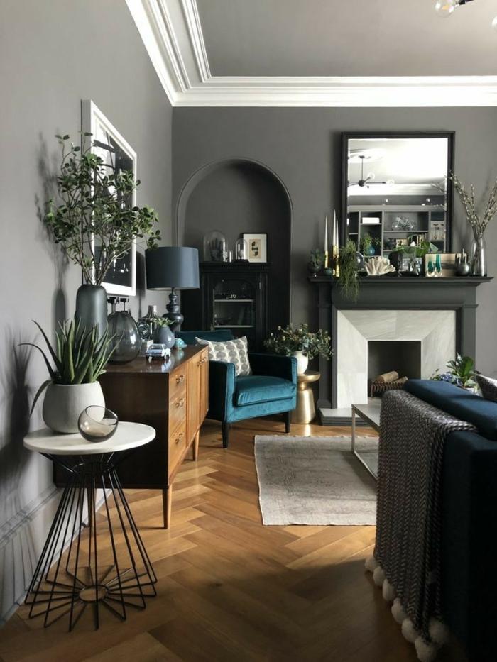 Raum mit viele Pflanzen, Holzboden, graue Wand, moderne Inneneinrichtung Spiegel über dem Kamin, Einrichtungsideen Wohnzimmer