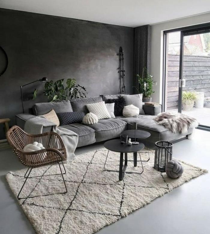 Ecksofa in grau mit Kissen in verschiedene Farben, zwei kleine Tische in schwarz, dunkle Wand, Wohnzimmereinrichtungen
