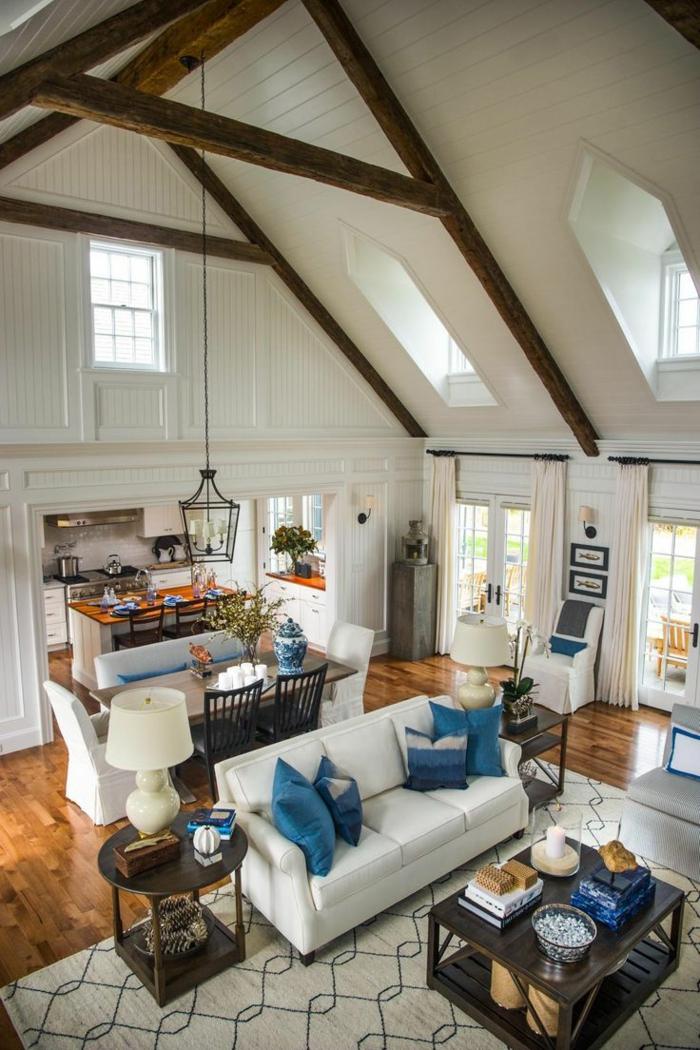 hohe Decke, sichtbare Balcken, weißes Sofa mit blauen Kissen, einrichtungsideen Wohnzimmer, Holztische, blaue Motive