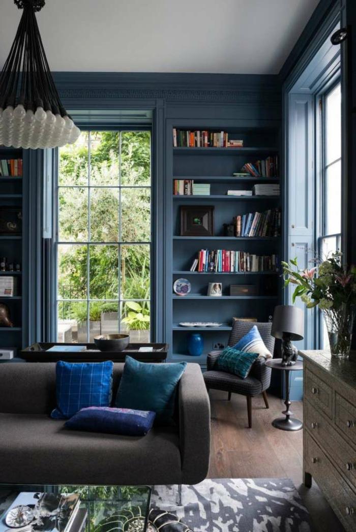 blaues Zimmer, Stellage mit Bücher, modernes Sofa, Kronleuchter mit sichtbaren Glühbirnen, Wohnzimmereinrichtungen