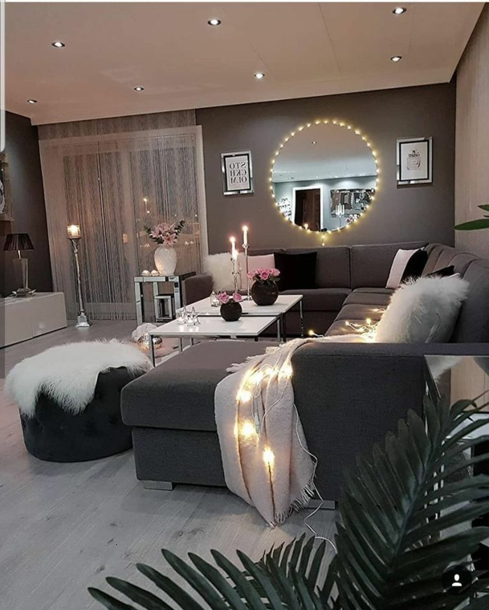 romantische und gemütliche Inneneinrichtung mit kleinen Lichtern, großes Sofa, runder Spiegel, Wohnzimmer gestalten