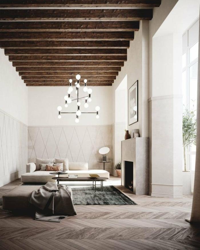 Inneneinrichtung im industrial chic Stil, sichtbare Balken, Kronleuchter, Holzboden, grünlicher Teppich, moderne Wohnzimmermöbel, Kamin