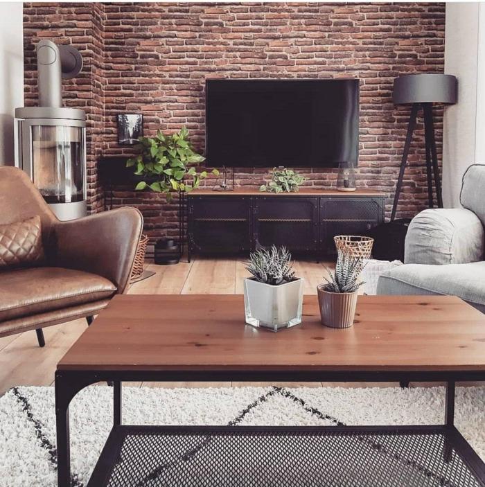 Industrialer Stil der Einrichtung, Ziegelwand, kleines Wohnzimmer einrichten, Sessel aus Leder, Kaktus Blumen