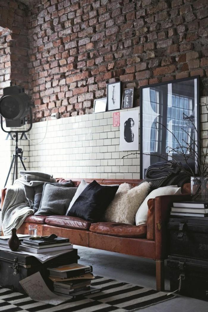 Backsteinwand in rot, Wohnzimmer einrichten beispiele, Ledersofa mit Kissen, schwarz-weißer Teppich